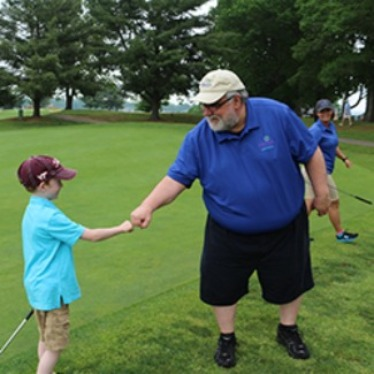 CVFCU CEO fist bumping CMN spokeskid on golf course