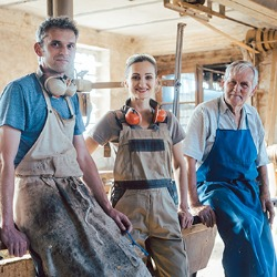 two men and a woman dressed for working in a carpentry shop smile for the camera