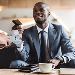 Man in suit at coffee shop paying with credit card