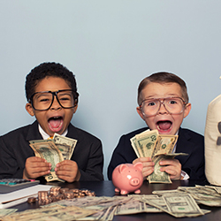 Two kids dressed in suits playing with money