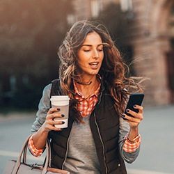 Woman walking with coffee cup in one hand and cell phone in the other