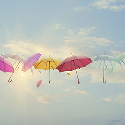 Fanciful umbrellas floating in blue sky