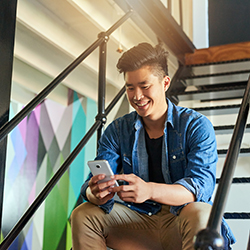 Young man sitting on staircase using smartphone