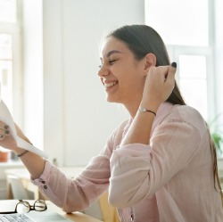 Young woman excitedly looking at paperwork
