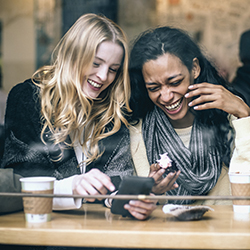 Two girls laughing in coffee shop with phone in hand