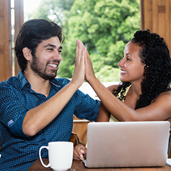 Couple high-fiving each other over laptop