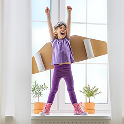 Young girl with cardboard rocket celebrating